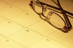 Calendar with glasses resting in yellow light